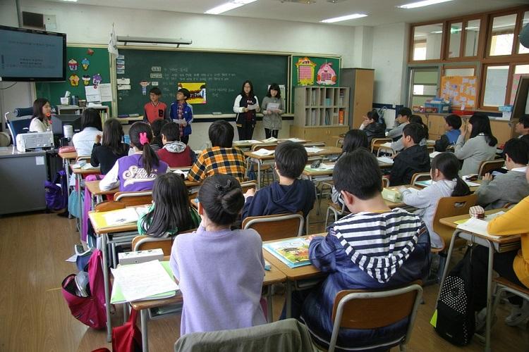 Sala de aula vista do fundo, com uma professora lecionando e os alunos virados na direção dela