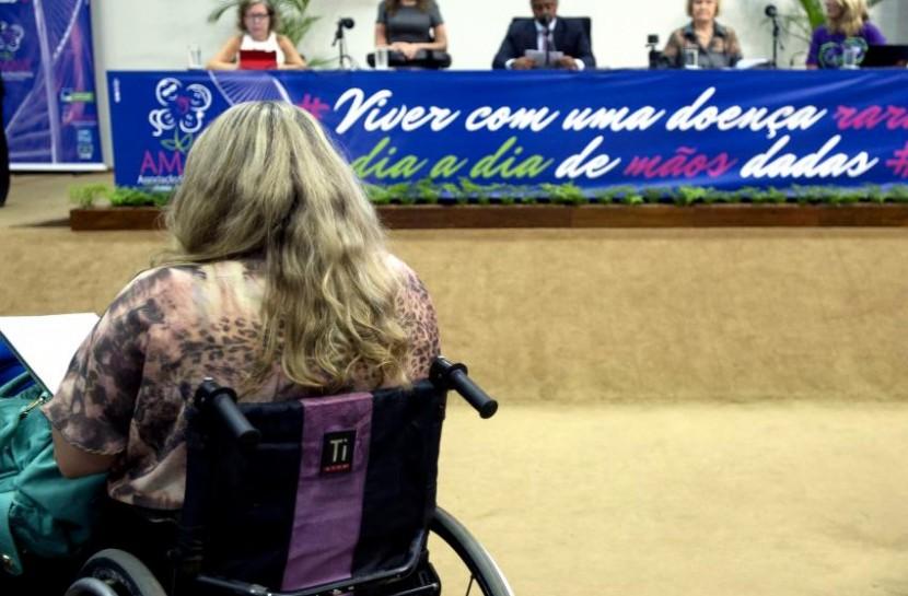 Em audiência da Câmara sobre mudanças na lei de cotas, uma mulher está de costas para a câmera, em sua cadeira de rodas. À sua frente, está a bancada de deputados.