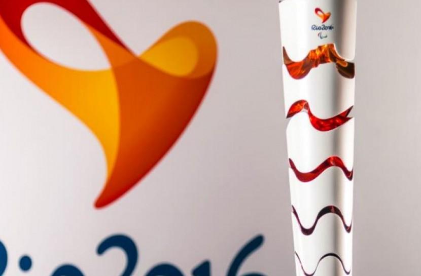 Foto da tocha em primeiro plano, com parte do logo Rio2016 ao fundo. A tocha é branca e recortada em seções horizontais e onduladas.