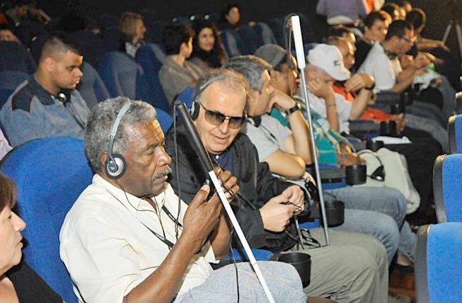 Foto de uma sala de cinema, com várias poltronas. Nelas, estão sentados homens de várias idades, que acompanham a exibição por meio de óculos e fones de ouvido para acessibilidade