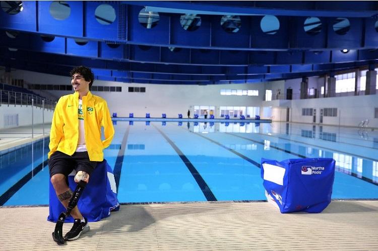 Foto de um ginásio coberto. Há uma piscina olímpica e, à frente, está um rapaz com uma prótese na perna esquerda. Ele veste uma jaqueta dada delegação brasileira, na cor amarela.