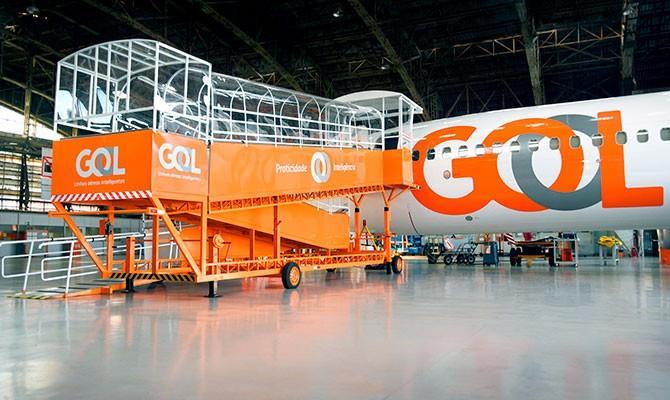 Foto de uma aeronave pousada em galpão, com uma rampa móvel acessível ao lado