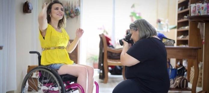 Foto de uma jovem cadeirante sorrindo e posando para a fotógrafa que a clica em uma sala ampla e iluminada