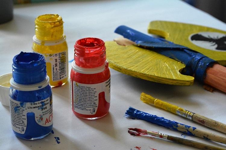 Em uma bancada, três frascos de tintas estão abertos, ao lado, há pincéis sujos e um paleta para misturar as cores