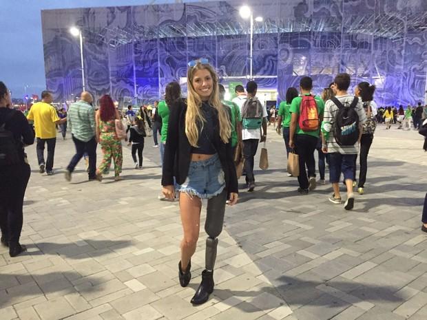 Uma mulher jovem, de longos cabelos loiros, sorri em frente a uma das entradas do Parque Olímpico, com grande movimentação de pessoas ao fundo. Ela usa uma prótese da perna esquerda.