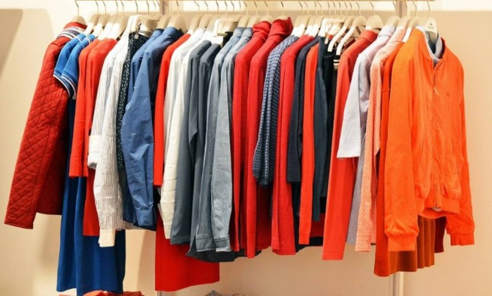 Uma arara de roupas com várias peças como camisas e jaquetas, em tonalidades de vermelho e laranja