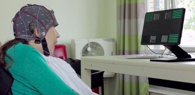 Uma mulher com mobilidade reduzida, sentada em uma cadeira, com uma touca cheia de eletrodos; ela olha na direção de um monitor de computador