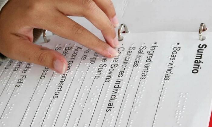 Foto de uma jovem mão feminina tateia um cardápio com informações em braile