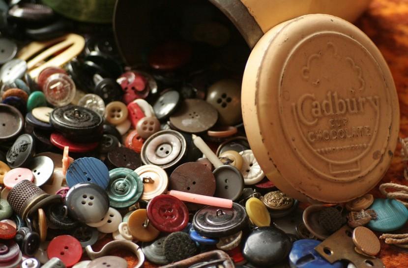 Diversos botões de lata e vintage espalhados em uma mesa