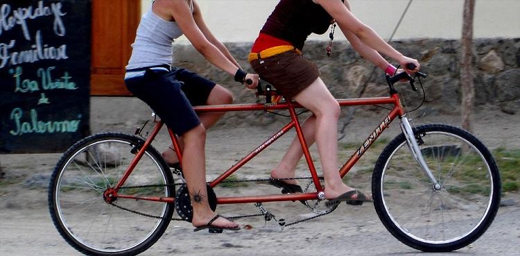 Foto de uma bicicleta modelo tandem, com dois espaços para banco, um guidón atrás do primeiro banco e dois conjuntos de pedais