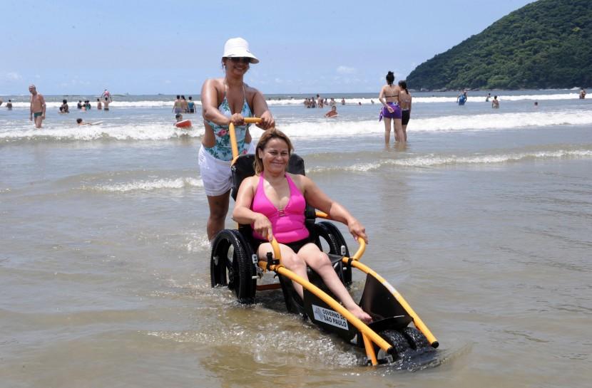 Em uma praia, uma jovem mulher, branca, está sentada em uma cadeira de rodas adaptada à água, com pneus de borracha e suporte para as pernas ficarem esticadas. Uma outra mulher, um pouco mais velha, empurra a cadeira saindo do mar