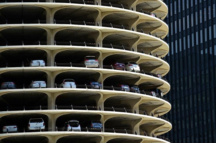 Foto de um estacionamento vertical; há vários andares sem paredes com carros estacionados
