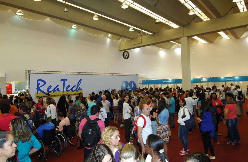 Multidão na frente da área de entrada da Reatech. No canto esquerdo da imagem, grande banner com o nome do evento Reatech.