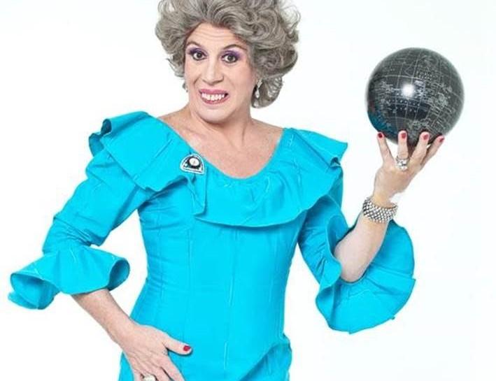 Foto do ator Eduardo Martini vestido no personagem Neide. Ele está com um vestido azul turquesa, uma peruca grisalha, maquiagem e dentadura. Está com uma mão na cintura e outra segurando um globo terrestre em uma das mãos.