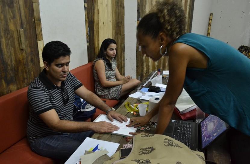 Foto de uma sala de aula, com uma longa bancada. Uma mulher está de pé e orienta um dos alunos, um homem cego que está sentado. Ao lado dele, há uma jovem.
