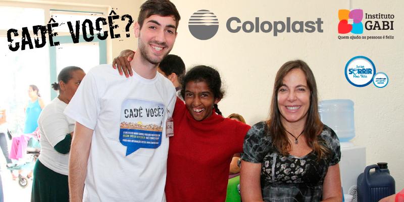 um jovem com a camiseta do projeto está ao lado de uma das atendidas, que apoia os braços nele e na fundadora do IMG, Mara Gabrilli, que está do outro lado. Os três estão sorrindo.