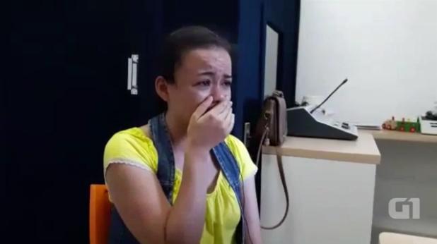 Em ambiente interno, mulher está sentada e chora emocionada, com a mão direita cobrindo a boca.