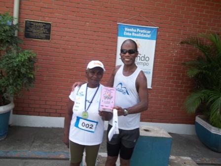 Foto da senhora Dona Maria de Lourdes ao lado do seu filho Rogério no pódio. Os dois estão posando para a foto, sorrindo. Ela usa uma medalha e roupa de corrida e segura um troféu com Rogério.