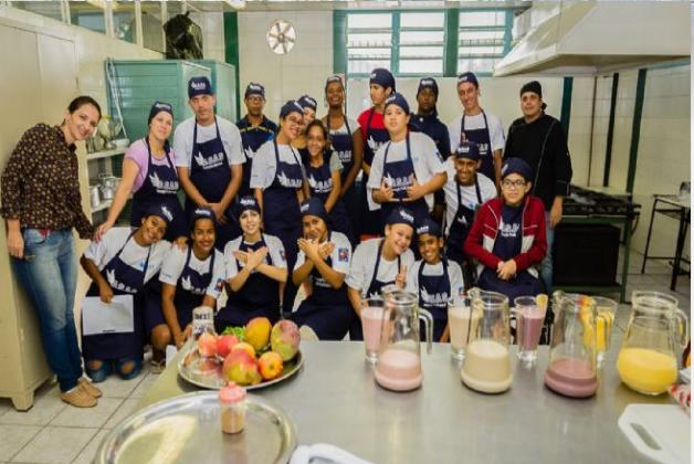 Foto de um grupo de jovens com cerca de 15 anos, em uma cozinha industrial. Eles usam toucas e aventais e posam juntos, sorrindo para a foto.