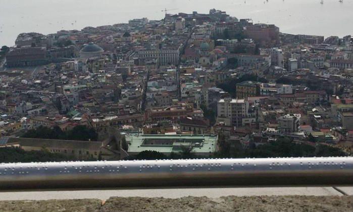 Foto em plano aberto da paisagem panorâmica da região da Campânia. No destaque, o corrimão com inscrições em braile