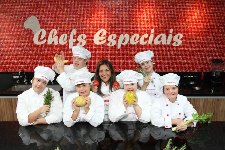 Foto de uma cozinha, com um grupo de seis alunos com Síndrome de Down, de aproximadamente 10 anos de idade, e uma jovem professora ao centro. Todos posam para a foto segurando ingredientes e vestem domãs e chapéus de cozinheiros