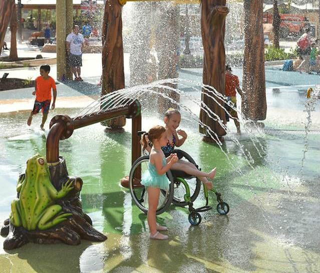 Foto de um parque aquático com duas garotas de aproximadamente 5 anos, uma delas cadeirante, brincando em um chafariz.