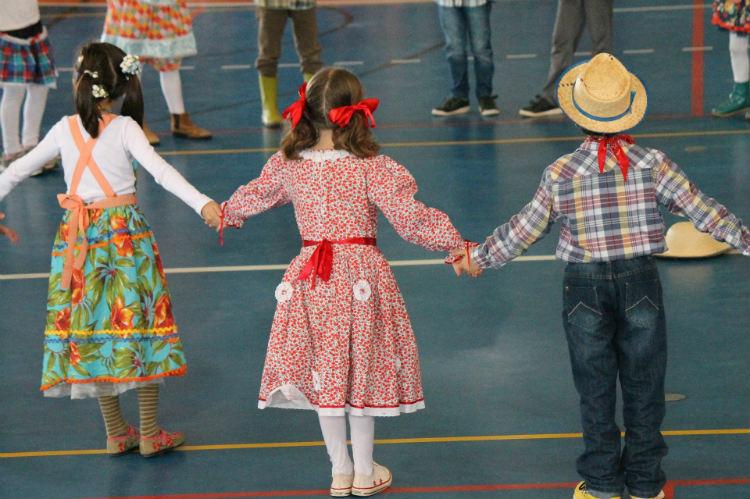 Foto de crianças, duas meninas e um menino, de aproximadamente 8 anos, vestidas com roupas típicas de caipira, de mãos dadas, dançando quadrilha.