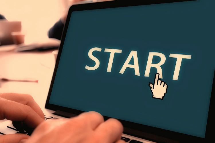 Foto aproximada de mãos digitando em um notebook. Na tela do aparelho, a palavra start e o cursor do mouse, representado por uma mão com o dedo indicador para cima.