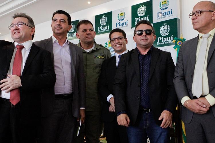 Foto de um com seis homens, posando para foto. Ao centro, há um cego com óculos escuros e bengala