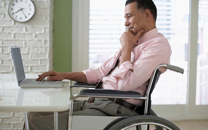 Foto de um senhor negro, sentado em uma cadeira de rodas, olhando curioso a tela de um notebook