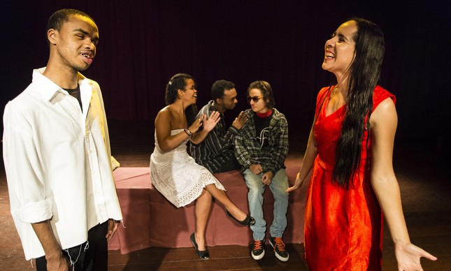 """Foto do espetáculo """"Dá um tempo pra falar de tempo"""". Em um palco, duas pessoas, um jovem negro e uma jovem branca com cabelos escuros, interagem. Ao fundo, há dois homens e uma mulher sentados em um banco, conversando"""