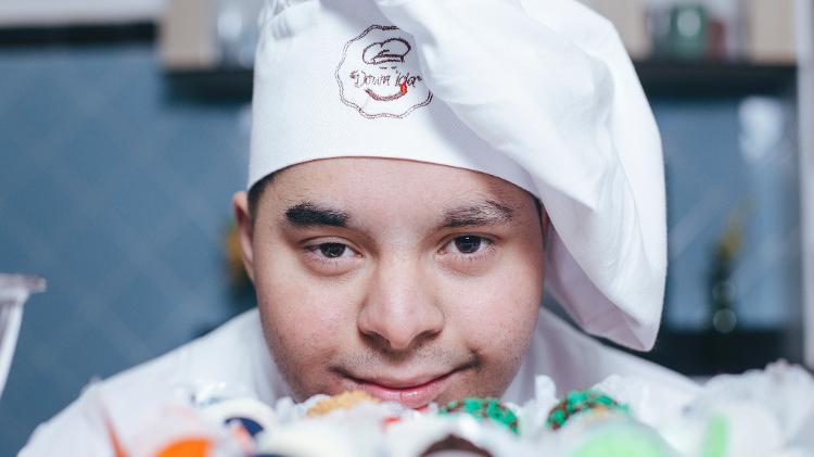 Foto em close de um jovem com síndrome de down, olhando na direção da câmera. Ele usa chapéu de cozinheiro e domã e tem uma expressão alegre e serena