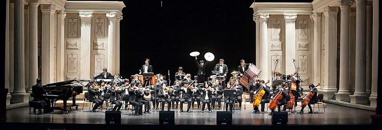 Foto de uma orquestra formada por pessoas de diversas idades. Eles usam trajes à rigor e estão disposto uniformemente em um palco com pé direito elevado