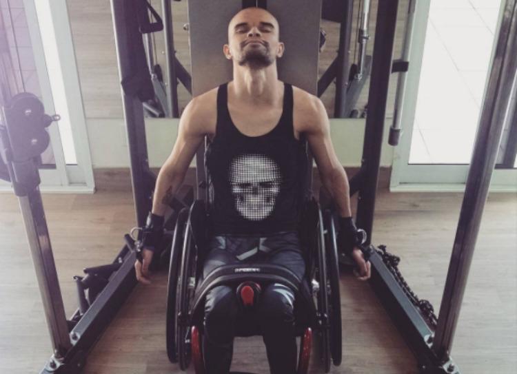 Foto de um homem moreno, musculoso e cadeirante, de 26 anos. Ele usa uma regata preta e faz exercícios para o braço em um aparelho de musculação