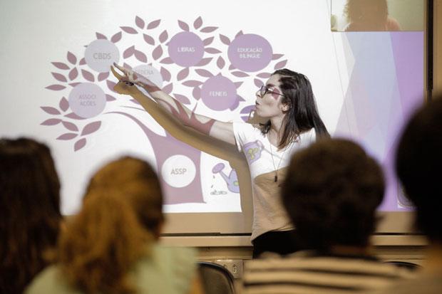 Foto da uma jovem branca, com cabelos castanhos e óculos apontando para palavras dentro de uma ilustração de árvore, em uma apresentação projetada na parede.