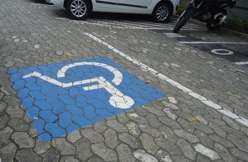 Foto de uma vaga de estacionamento exclusiva para pessoa com deficiência, com o símbolo de um cadeirante pintado em azul e branco