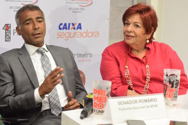 Foto do Senador Romário, um homem de meia idade, negro, com terno e gravata cinza, ao lado de Diva Marinho, uma senhora de aproximadamente 65 anos, pele clara e cabelos vermelhos