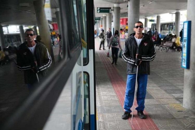 Foto de um terminal rodoviário. Um homem de meia idade, cego, com óculos escuros e uma bengala. está de pé, do lado de um ônibus