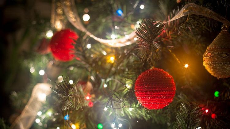 Foto do detalhe de uma árvore de natal, com bolas natalinas de linha vermelha e pisca-pisca