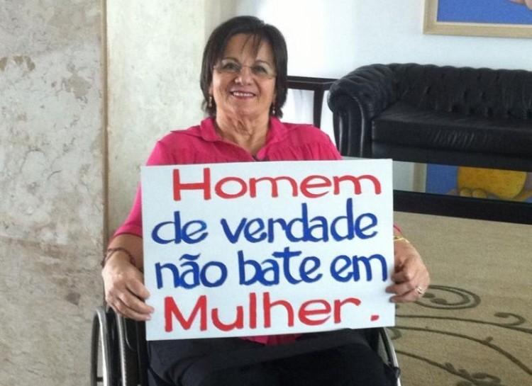 Foto de Maria da Penha, sentada em uma cadeira de rodas, segurando um cartaz com os dizeres: Homem de verdade não bate em mulher