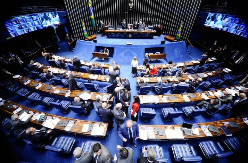 Foto de bancadas do Senado Federal vistas de cima. O chão é azul e as bancadas de madeira. Há grupos de pessoas caminhando e conversando por entre elas.