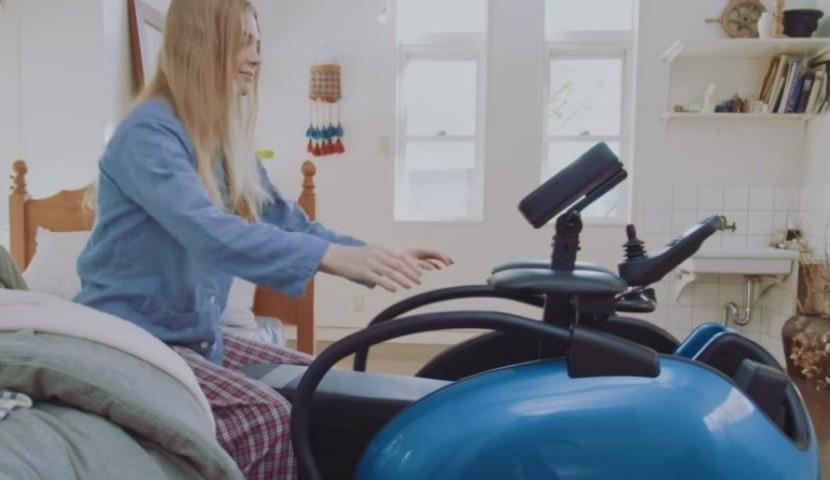 Foto de uma jovem mulher loira de pijamas, sentada na beira da cama. Perto dela, há uma cadeira motorizada, com uma base azul que indica o assento