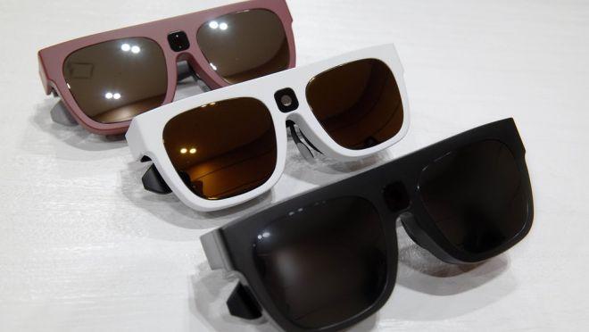 Foto de três óculos inteligentes. Eles possuem lentes escuras e retangulares, com opções de armações em rosa, branca e preta.