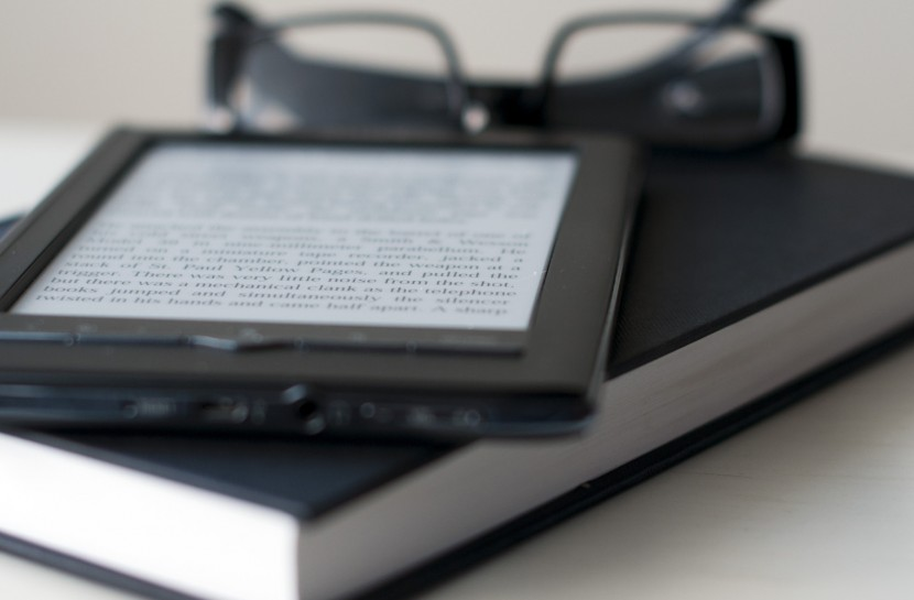 Foto de uma pilha com um leitor digital e um livro com um óculos de leitura fechado em cima