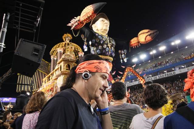 Foto de um homem com fones de ouvido com o sambódromo ao fundo e carros alegóricos