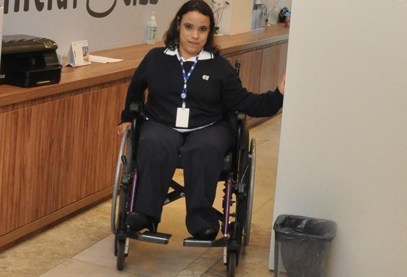 Foto da entrada do Inclui CIEE, com uma jovem cadeirante na porta. Ela está uniformizada, usa um crachá e sorri