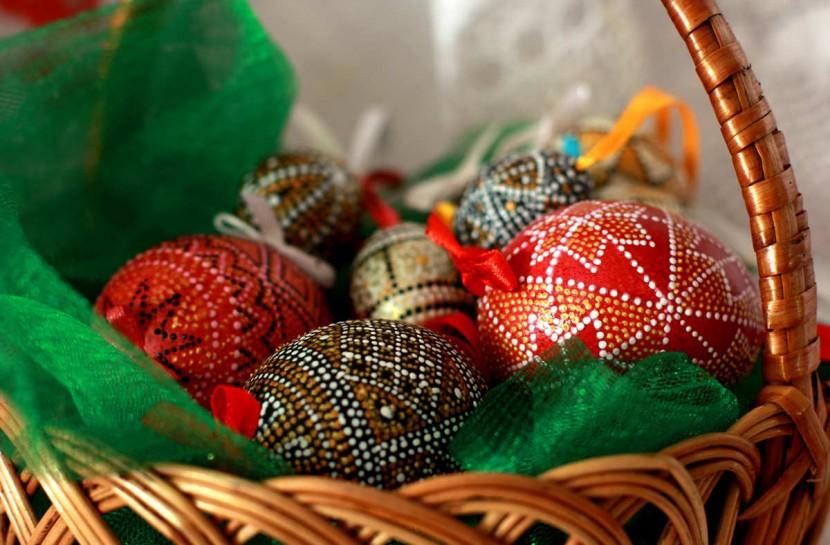 Foto em close de uma cesta com ovos de galinha pintados com adornos nas cores de vermelho e dourado