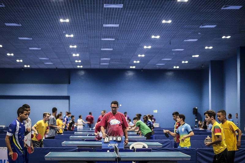 Foto de um grande salão com diversas mesas de tênis de mesa. Em destaque, um instrutor orienta dois garotos de aproximadamente 14 anos, que seguram raquetes