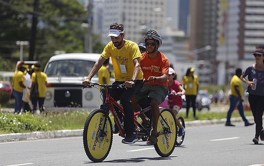 Foto de uma avenida, com dois homens jovens de capacete guiando uma bicicleta adaptada, com dois bancos e dois guidões