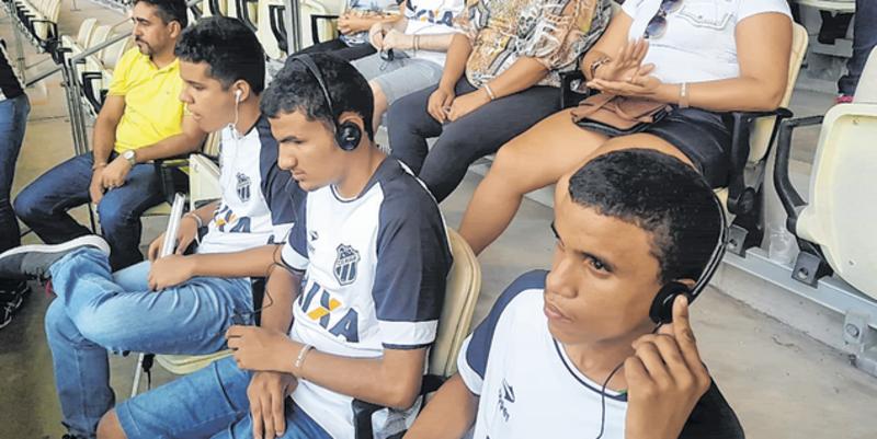 Foto de homens jovens com deficiência visual. Eles estão sentados na arquibancada com fones de ouvido